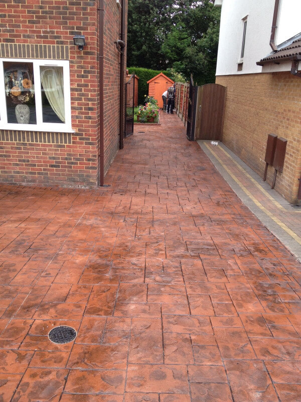 New concrete driveway in Stretford in a Terracotta stone printed in Ashlar cut and sealed in mid sheen