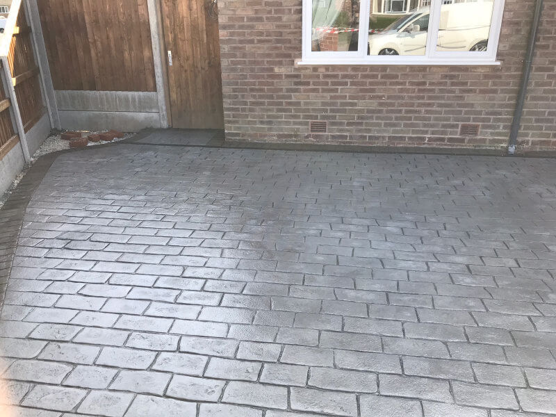 Pattern imprinted concrete driveway in Olde English Cobble with an acid stained edge